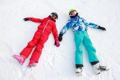 Девушки лежа на снеге Стоковая Фотография