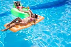 Девушки держа коктеили и лежа на тюфяке воздуха Стоковое Изображение RF