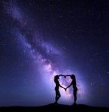 Девушки держа руки в форме сердца Ландшафт с млечным путем Стоковая Фотография RF