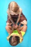 Девушки держа руки сидя на голубой предпосылке Стоковые Фотографии RF