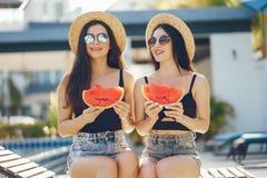 2 девушки есть арбуз Стоковая Фотография