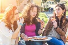 Девушки есть пиццу Стоковое фото RF
