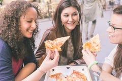 Девушки есть пиццу Стоковое Изображение