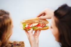 Девушки есть сандвичи Стоковая Фотография