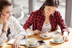 Девушки есть торт и выпивая кофе на кафе, перерыве на чашку кофе Стоковая Фотография