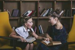 Девушки детей в библиотеке с книгами в образовании Стоковое Изображение RF