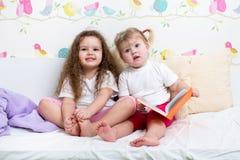 Девушки детей прочитали книгу в кровати Стоковое фото RF