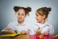 Девушки делают что-то от покрашенной бумаги используя клей и ножницы Стоковое Фото