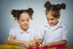 Девушки делают что-то от покрашенной бумаги используя клей и ножницы Стоковая Фотография RF