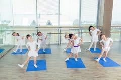 Девушки делая гимнастические тренировки или работая в классе фитнеса Стоковые Фото