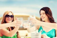 Девушки делая здравицу в кафе на пляже Стоковые Изображения