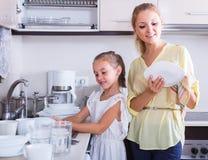 Девушки делая и обтирая блюда в кухне Стоковые Фотографии RF
