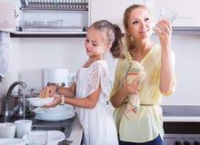Девушки делая и обтирая блюда в кухне Стоковое Изображение RF