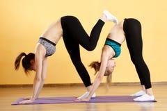 Девушки делая йогу на половике Стоковое Изображение