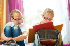 Девушки делая домашнюю работу и пакуя сумки школы Стоковая Фотография