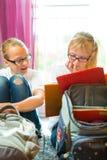 Девушки делая домашнюю работу и пакуя сумки школы Стоковая Фотография RF