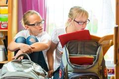 Девушки делая домашнюю работу и пакуя сумки школы Стоковое Изображение