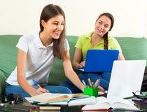 Девушки делая домашнюю работу на кресле Стоковое Изображение RF