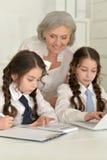 Девушки делая домашнюю работу с бабушкой Стоковое фото RF