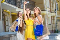Девушки делая selfie Девушки держа хозяйственные сумки и прогулку вокруг Стоковое фото RF
