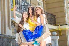 Девушки делая selfie Девушки держа хозяйственные сумки и прогулку вокруг Стоковые Изображения