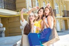 Девушки делая selfie Девушки держа хозяйственные сумки и прогулку вокруг Стоковая Фотография RF