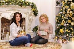 Девушки ждут приятные сюрпризы Нового Года и sittin Стоковое фото RF