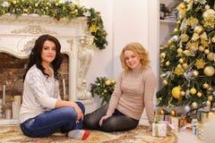 Девушки ждут приятные сюрпризы Нового Года и sittin Стоковое Фото