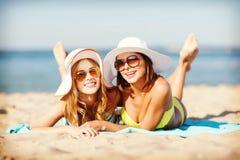 Девушки загорая на пляже Стоковое Фото