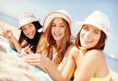 Девушки загорая на пляже Стоковые Изображения