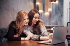2 девушки занимаясь серфингом сеть, вывешивая на социальные сети на портативном компьютере и имея потеху Стоковые Фотографии RF