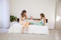 3 девушки играют сестер в утре на кровати в спальне Стоковые Изображения