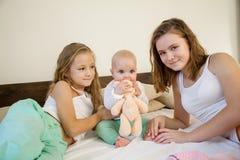 3 девушки играют сестер в утре в спальне Стоковые Изображения RF