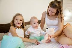 3 девушки играют сестер в утре в спальне Стоковые Фотографии RF