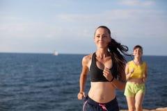 Девушки играют спорт бежать вокруг на пляже Стоковое фото RF