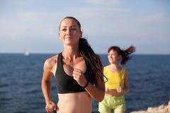 Девушки играют спорт бежать вокруг на пляже Стоковые Фото
