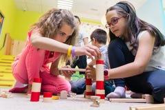 2 девушки играя вместе с деревянными блоками игрушки на поле на детском саде Стоковое Изображение