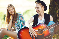 Девушки играя гитару в парке Стоковое Фото