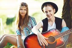 Девушки играя гитару в парке Стоковые Фото