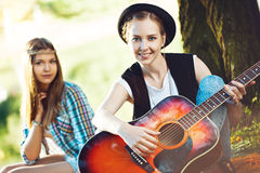 Девушки играя гитару в парке Стоковые Фотографии RF