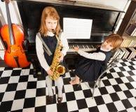 Девушки играя на саксофоне и рояле альта Стоковые Изображения RF