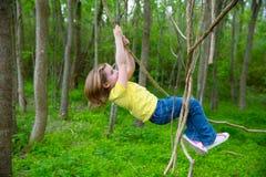 Девушки играя смертную казнь через повешение в лианах на парке джунглей Стоковая Фотография