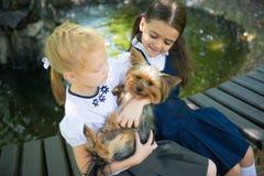 2 девушки играя с собакой Стоковое Изображение