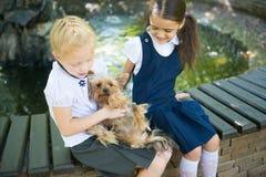 2 девушки играя с собакой Стоковая Фотография