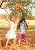 Девушки играя с упаденными листьями Стоковые Изображения RF
