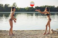Девушки играя с шариком на пляже Стоковое фото RF