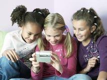 Девушки играя с электрическим устройством Стоковое Изображение