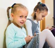 Девушки играя с smartphones Стоковые Изображения