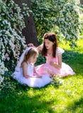 Девушки играя dressup в sunlit саде Стоковое Изображение RF