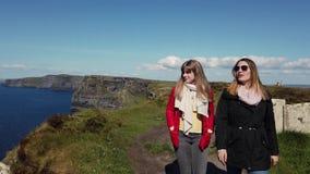 2 девушки идут вдоль края известных скал Moher акции видеоматериалы